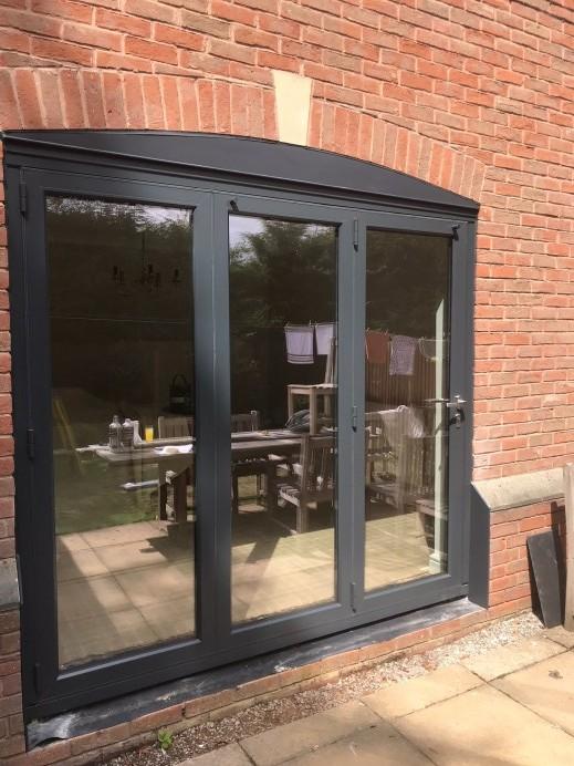 Origin Bi Fold Doors Installed in a Property, With an Orangery Installed in the Garden